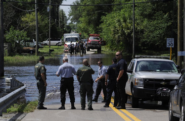 Emergency crews work scene of a street covered with floodwaters from Tropical Storm Debby in New Port Richey