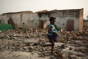 A girl walks through the rubble of demolished Muslims' homes in the district of Miskine in Bangui