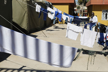 An African migrant  sits next to clothes lines in a refugee centre in Spain's north African enclave Melilla