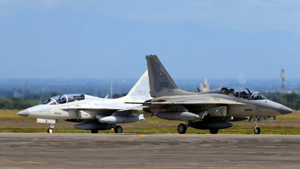 A FA-50 fighter jet, newly purchased from South Korea, is escorted by a fighter jet upon arrival at a hangar in Clark air base, Angeles city, Pampanga province, north of Manila