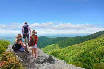 People with backpacks hiking on summer trip in mountains. Father with his family enjoying time on a trip. Close to Asheville, Blue Ridge Mountains, North Carolina, USA.