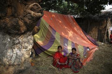 "Women sit outside their tent during the ""Gadhimai Mela"" festival held in Bariyapur"