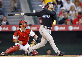 Toronto Blue Jays' Lind hits a sacrifice fly as Los Angeles Angels catcher Napoli looks on during their MLB American League baseball game in Anaheim