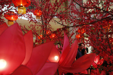 A couple poses for a photograph in front of Chinese New Year decorations in one of Kuala Lumpur's largest shopping malls