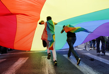 Protesters run under a huge flag during the Athens Pride Parade in Athens