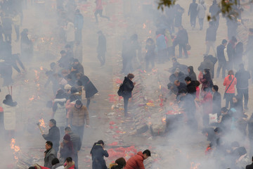 People burn incense to worship the God of Fortune at Guiyuan Temple on the fifth day of Chinese Lunar New Year, in Wuhan