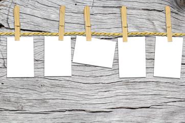 cinq cartes blanches sur corde à linge, fond bois blanchi