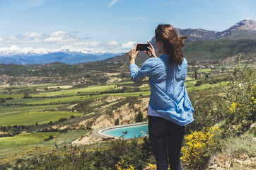 Fotomurales - Hipster photograph on smart phone gadget mobile, mock up of blank screen. Girl traveler hold in hand mobile on background mountain landscape horizon. Tourist look map on adventure trip