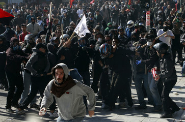 Black-clad youths beat a communist near the Parliament building in Syntagma (Constitution) square in Athens
