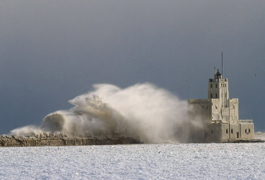A light house is pounded by waves on Lake Michigan