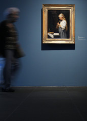 """A woman walks past the painting """"Maedchen, die Haare flechtend"""" by late Swiss painter Albert Anker during a media preview of the exhibition """"Beautiful World"""" in Bern"""