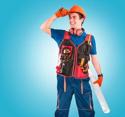 Handsome young handyman with a tool belt looking on a left. House renovation service. Building concept.