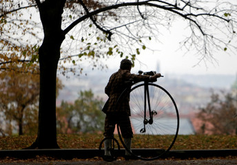 A man wearing a historical costume pushes his high-wheel bicycle before the annual penny farthing race in Prague