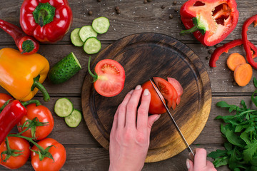 Female hands cutting tomato at table, top view