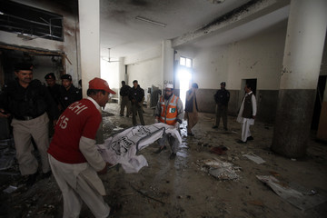 Rescue workers carry the covered body parts of a suspected suicide bomber at the site of bomb blast in a judicial compound in Peshawar