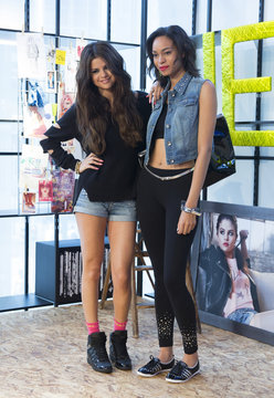 U.S. actress and singer Gomez poses with model wearing pieces of collection she has created for Adidas Neo label during its presentation in Berlin
