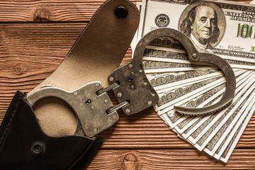 Handcuffs from a leather holster lie on banknotes 100 dollar. The idea: a crime, detention of the attacker. court. deprivation of liberty. arrest. Business, bribery, corruption.