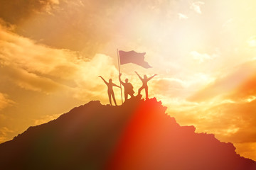 High achiever, silhouettes of three people holding on top of a mountain to raise their hands up. A man on top of a mountain. Conceptual design. Against a dramatic sky with clouds at sunset.