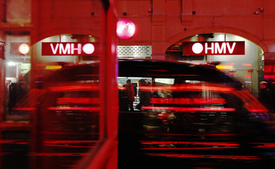 A HMV music branch is partly reflected in a telephone box in London