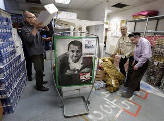 "Volunteers carry food near a picture of late French comic Coluche in a charity food distribution centre ""Les Restos Du Coeur""  in Nice"