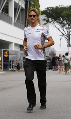 McLaren Formula One driver Button of Britain runs through the paddock before the Singapore F1 Grand Prix
