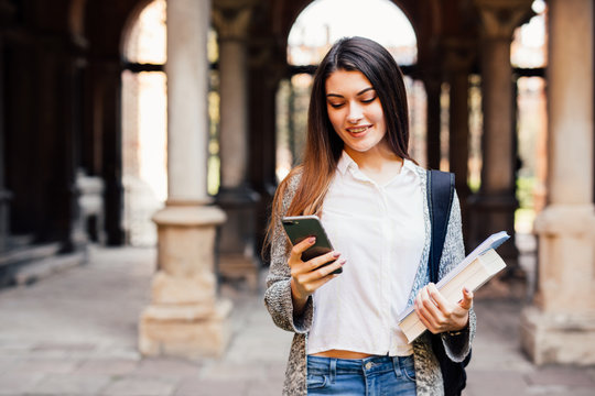 Student girl read something on smartphone outdoor near University