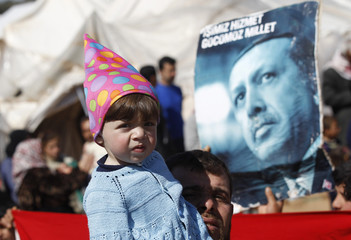 A Syrian refugee girl, with a poster of Turkey's Prime Minister Erdogan in the background, attends a protest against Syria's President Bashar al-Assad at Reyhanli refugee camp