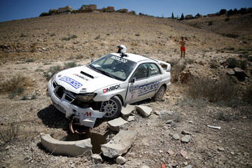 A man takes pictures of a smashed rally car during a sprint-rally race held in the southern city of Arad