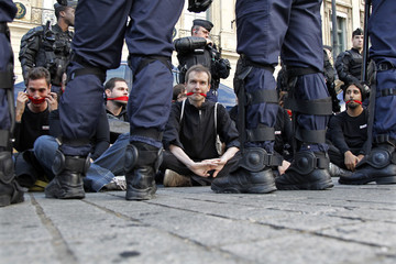 Reporters Without Borders activists are surrounded by riot policemen in front of the Ritz hotel in Paris