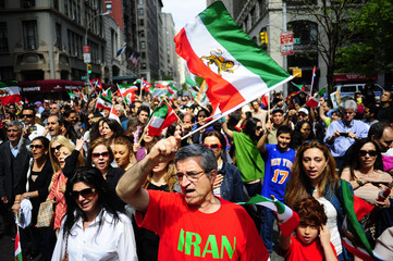 Marchers carry pre-Islamic Revolution flags of Iran as they march in the Persian Day Parade in New York
