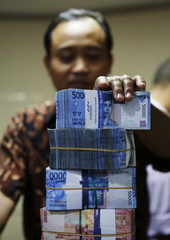 A money changer stacks Indonesian rupiah notes as he serves a customer in Jakarta