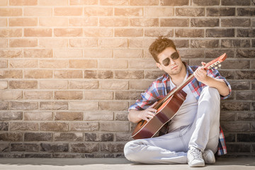 Fashionable acoustic guitar player sitting on ground and leaning against the brick wall outdoors