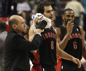 Raptors guard Calderon is helped from the floor near teammate Anderson after sustaining an injury while playing against the Philadelphia 76ers during the first half of their NBA basketball game in Philadelphia