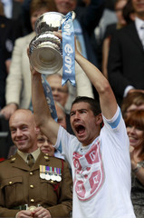 Manchester City's Aleksandar Kolarov lifts the trophy after his team defeated Stoke City in their FA Cup final soccer match at Wembley Stadium