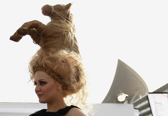 Model wearing hat designed from hair in shape of horse, poses during 17th Dubai World Cup at Meydan racecourse in Dubai