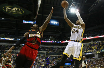 Indiana Pacers Paul George shoots the ball while being defended by Atlanta Hawks Josh Smith during their NBA basketball game in Indianapolis