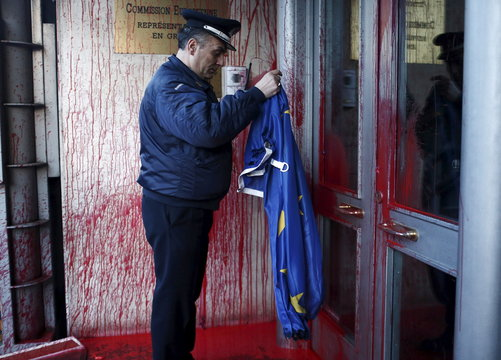 A police officer holds an EU flag at the European Commission office, which is splattered with red paint thrown by demonstrators, during a protest to raise awareness for the deaths of immigrants in the Mediterranean, in Athens
