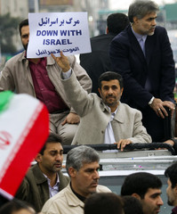 Iranian President Ahmadinejad holds a placard as he takes part in a rally to mark the 32nd anniversary of the Islamic Revolution in Tehran