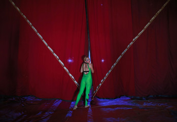 A female member of an acrobatic team looks from behind the curtains as she waits backstage before the start of her performance at the Rambo Circus in Mumbai