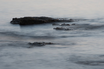 Rocks in the sea with smooth flowing water