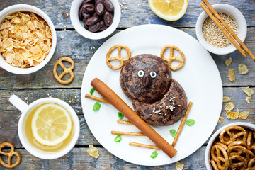 Food art for kids - funny koala on the tree from gingerbread, straw, pretzels, candy and cereal
