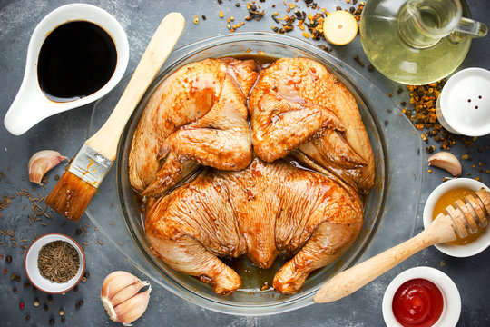 Raw marinated whole chicken for BBQ with soy sauce, honey, garlic, spices
