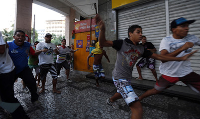 Demonstrators run away during protest against the Confederations Cup and the Brazil's government in Recife