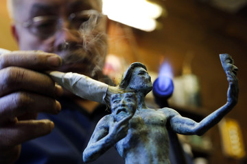 """Patina artist Joaquin Quintero applies a formula of salts and acids on the bronze metal in order to create the patina coloring on """"The Actor"""" statuette at American Fine Arts Foundry in Burbank"""