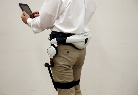 Honda Motor Co employee demonstrates the company's new Walking Assist Device, which for those with weakened leg muscles who are still able to walk, during its unveiling in Tokyo