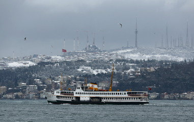 A ferryboat, with the snow-covered Camlica Hill in the background, moves along the Bosphorus in Istanbul