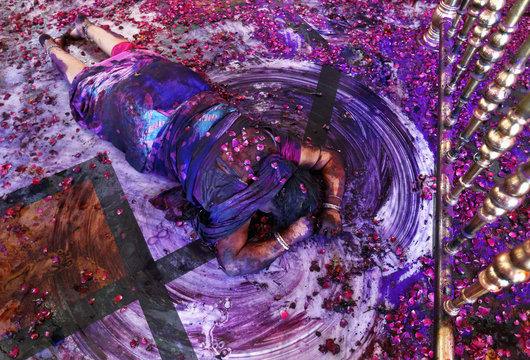 A Hindu woman prays while lying on the floor of a temple during Holi celebrations in Ahmedabad