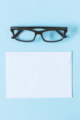 Glasses in dark frame and white blank envelope