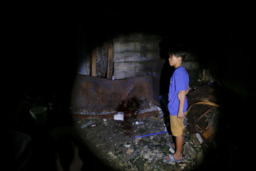 A boy arrives to the spot where his father was killed in a police operation shortly before in Manila