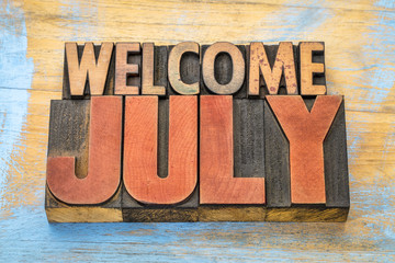 Welcome July word abstract in wood type